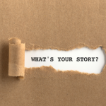 A piece of cardboard ripped revealing the words: what's your story?