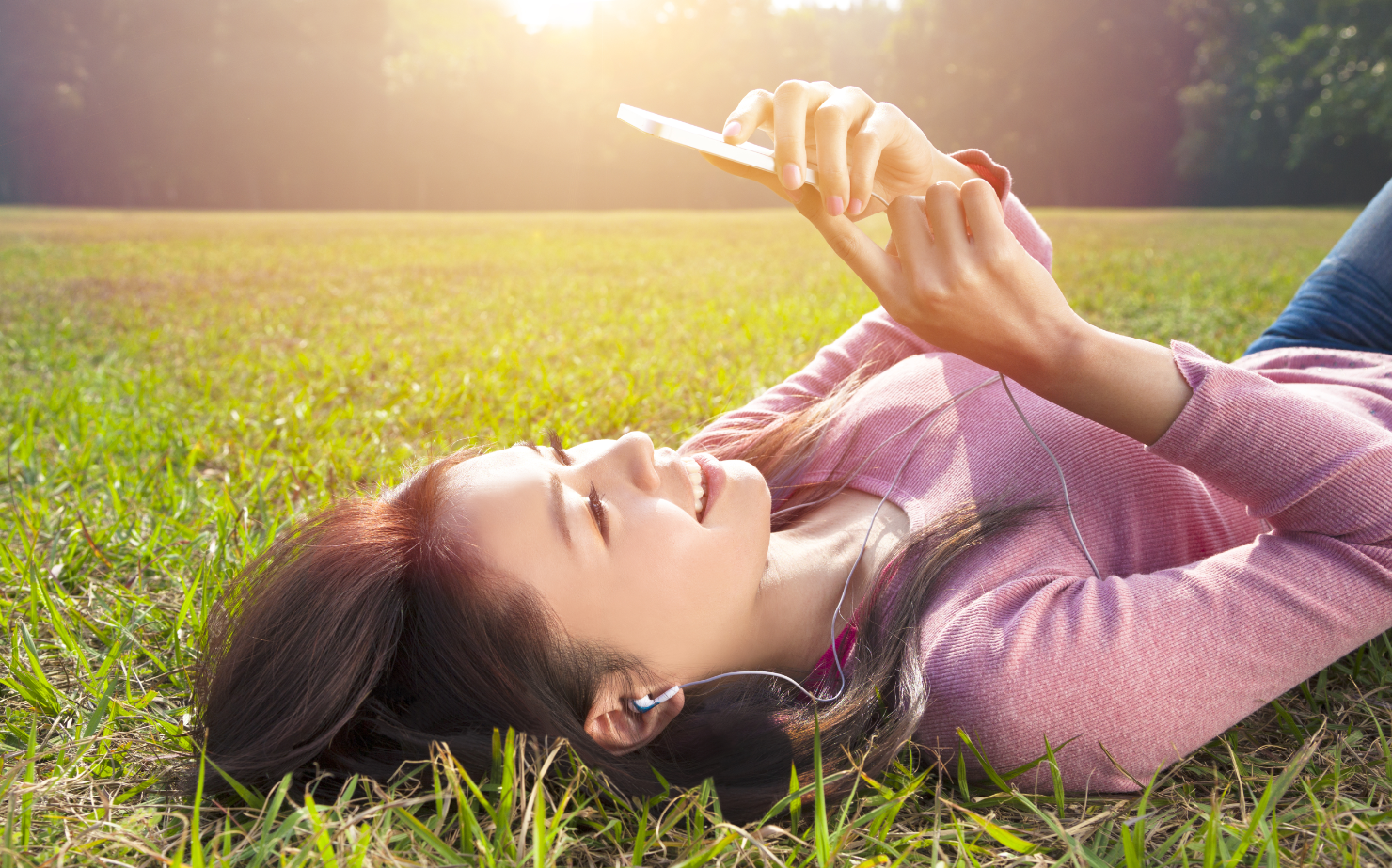 A woman in a sunny field lying on her back, looking at her phone after exercising.